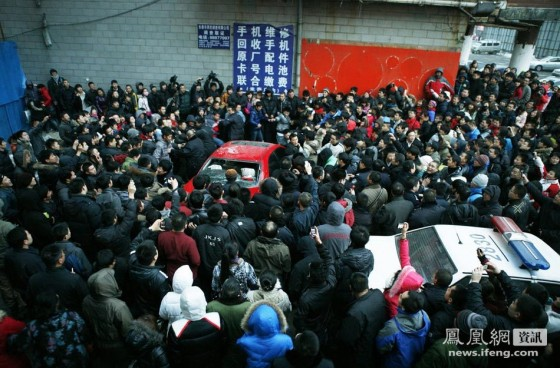 A large crowd surrounds a red Mazda6 in Changchun, China.